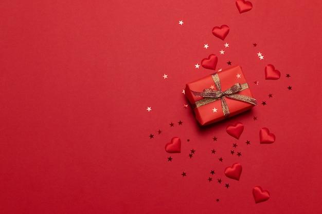 Carte de voeux de joyeuses fêtes avec des confettis d'étincelles paillettes d'or avec boîte-cadeau sur fond rouge. Photo Premium