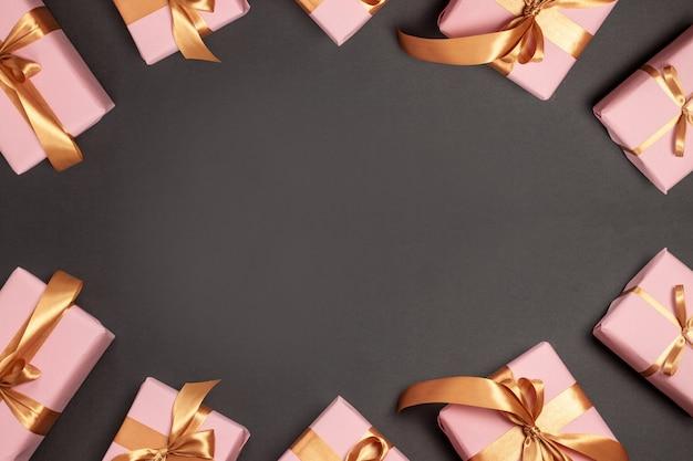 Carte De Voeux Joyeux Noël Et Joyeuses Fêtes Avec De Nombreux Cadeaux Surprise Avec Des Rubans D'or Sur Fond Sombre. Mise à Plat, Vue De Dessus Photo Premium