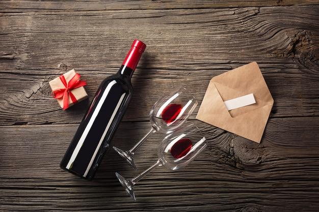 Carte De Voeux Saint Valentin. Vin Rouge, Coffret Cadeau Et Verres Sur Une Table En Bois Photo Premium