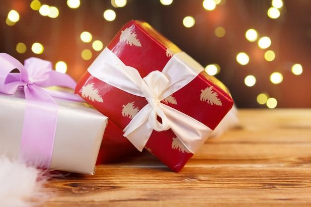 Carte de voeux de vacances avec des coffrets cadeaux sur fond de lumières brouillées Photo Premium