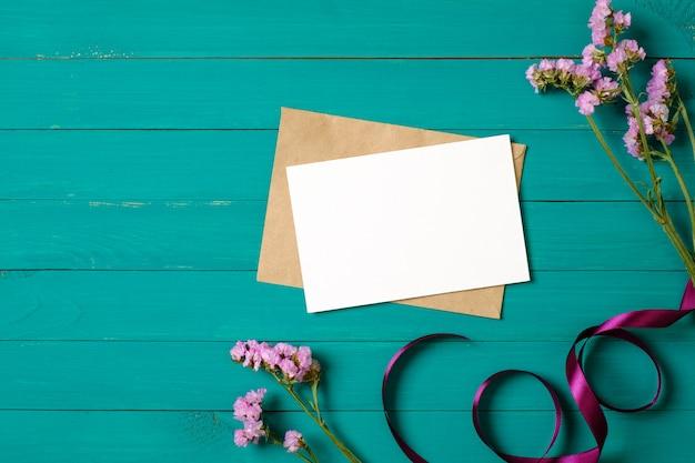 Carte De Voeux Vierge Et Enveloppe Avec Des Fleurs De Marguerite Pourpre Sur Une Table En Bois Verte. Composition Plate, Vue De Dessus, Frais Généraux. Photo Premium