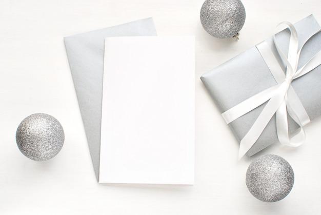 Carte De Voeux Vierge, Invitation Avec Enveloppe Argentée Et Cadeau Et Décorations Pour Noël. Photo Premium