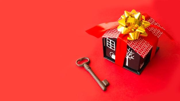 Carton maison avec un arc et un ruban près de la clé Photo gratuit