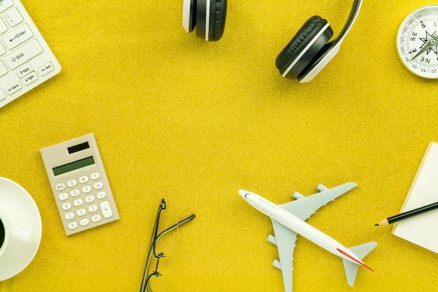 Casque d'écoute avec calculatrice, réveil blanc, boussole, maquette d'avion et tasse à café sur la texture de paillettes d'or fond brillant étincelant Photo Premium