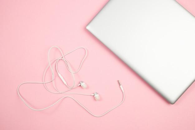 Casque Filaire Blanc Et Ordinateur Portable Sur Fond Isolé Rose. Vue De Dessus. Mise à Plat. Maquette Photo Premium