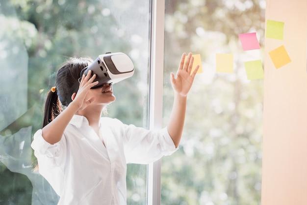 Casque d'interaction de réalité virtuelle par asian belle jeune femme vêtue d'un air touchant pendant la boîte vr pour jouer aux futurs médias du simulateur de jeu. concept numérique de technologie d'innovation futuriste Photo Premium