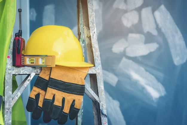 Casque jaune avec niveau d'eau, gants et radio placés sur l'échelle pliante. Photo Premium