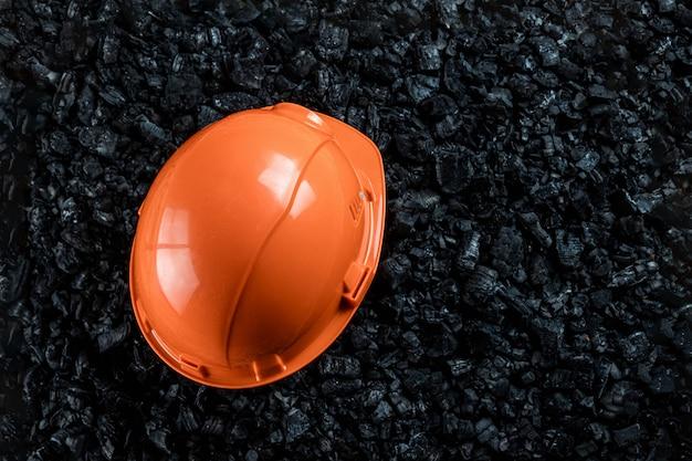 Un casque orange de mineur repose sur un tas de charbon, une mine de charbon à ciel ouvert, un espace de copie. Photo Premium