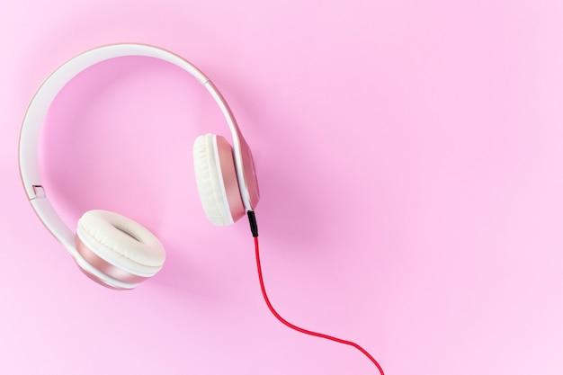 Casque rose et câble rouge sur fond de couleur rose pastel. concept de musique. Photo Premium