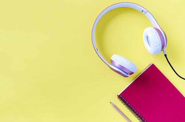 Casque rose, carnet et crayon sur fond de couleur jaune pastel. concept de musique. Photo Premium