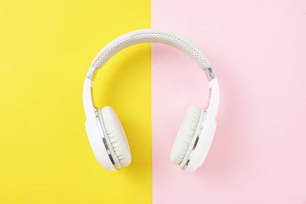 Casque sans fil blanc sur fond rose et jaune Photo Premium