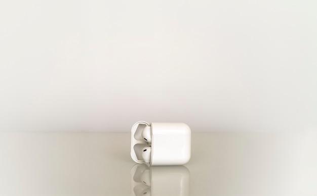 Casque Sans Fil Unique Blanc Dans La Zone De Charge Sur Dégradé Gris Avec Reflet Dans Le Verre De La Table Photo Premium