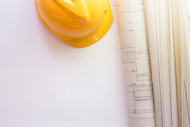 Casque de sécurité et blueprint sur fond blanc. vue de dessus avec copie sapce. Photo Premium