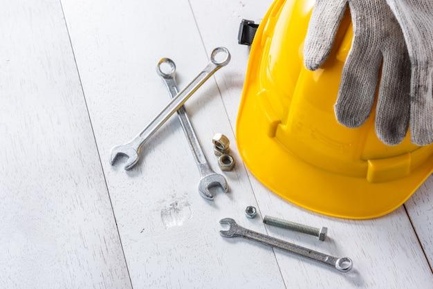 Casque de sécurité jaune et outils sur une table en bois blanche Photo Premium