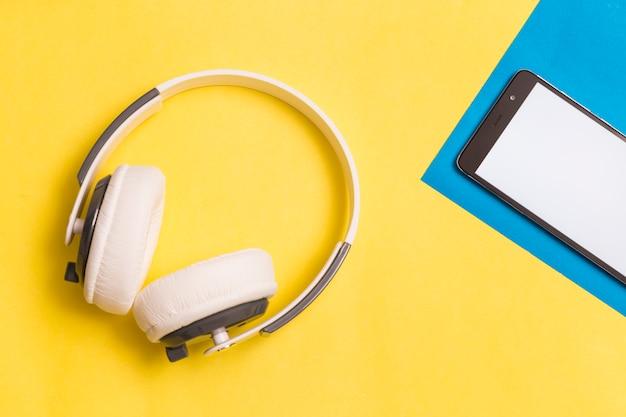 Casque et smartphone sur fond coloré Photo gratuit