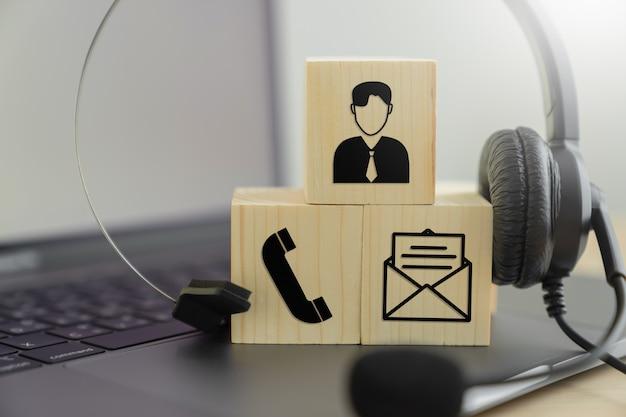 Casque Voip Et Communication Par Icône Sur Le Bloc De Bois. Support De Centre D'appels Concept. Photo Premium