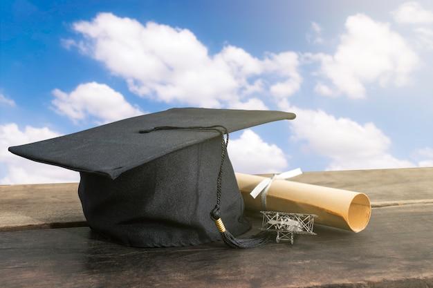Casquette de graduation, chapeau avec papier degré sur table en bois Photo Premium