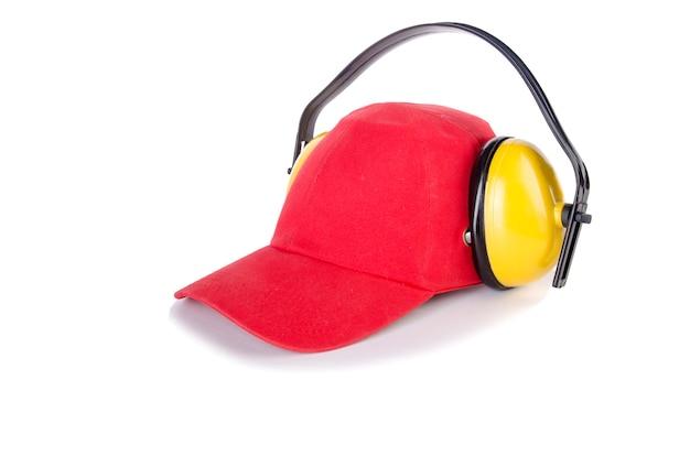 Casquette rouge avec des écouteurs de bruit isolés on white Photo Premium