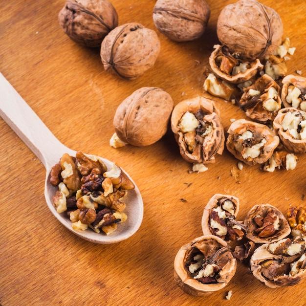 Cassé; noix et noyau entiers sur cuillère en bois Photo gratuit