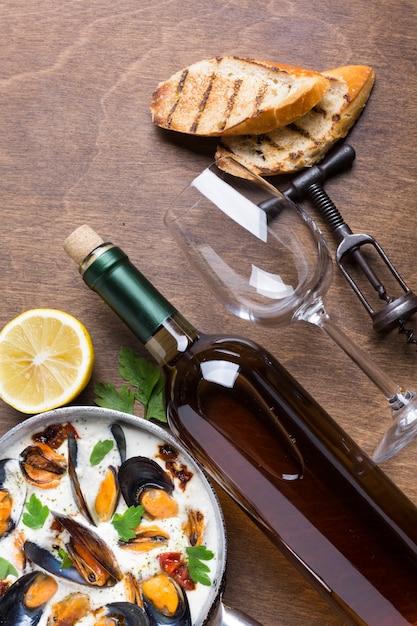 Casserole plate avec moules en sauce blanche avec bouteille de vin Photo gratuit