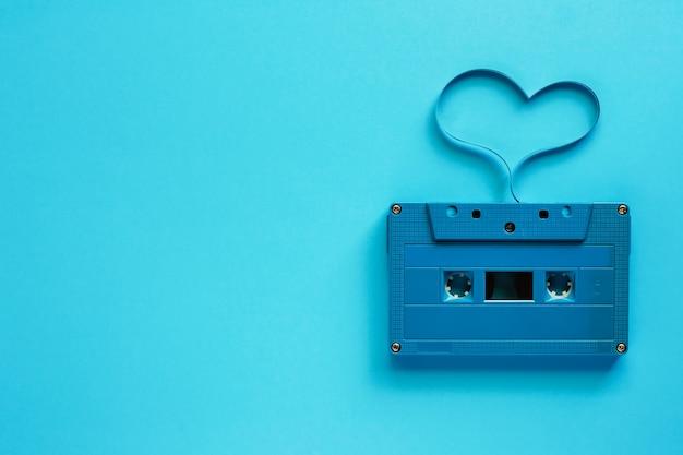 Cassette audio rétro avec forme de coeur sur fond bleu pour la musique et le concept de l'amour Photo Premium