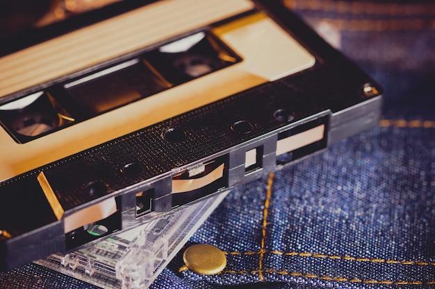 Cassette audio sur un tissu de jeans dans l'obscurité. lecteur de musique vintage des années 90. Photo Premium