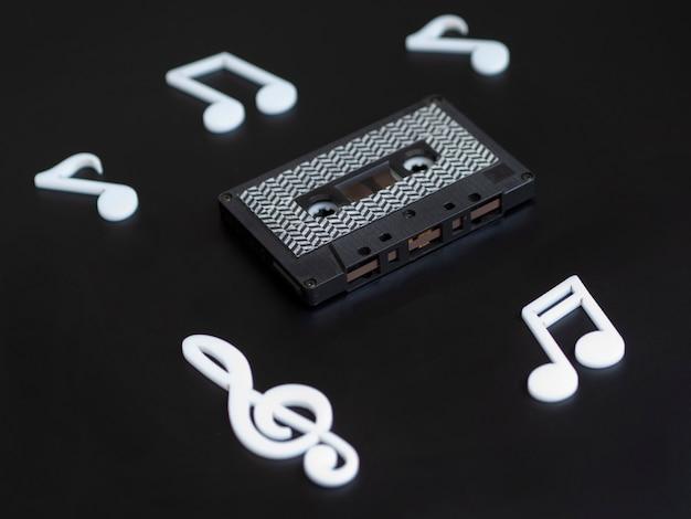 Cassette noire sur fond sombre avec des notes Photo gratuit