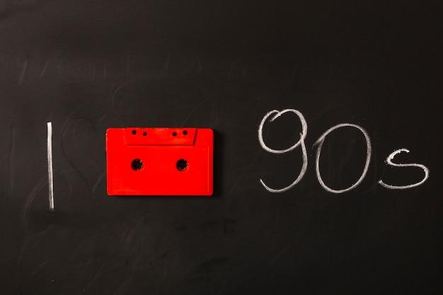 Cassette rouge avec années 1990 écrit sur tableau noir Photo gratuit
