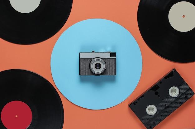 Cassette Vidéo Disque Vinyle Rétro, Appareil Photo Argentique Sur Fond De Couleur Corail Avec Un Cercle Bleu. Vue De Dessus Photo Premium