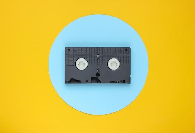 Cassette Vidéo Sur Fond Jaune Avec Cercle Pastel Bleu. Concept Rétro Minimaliste. Photo Premium