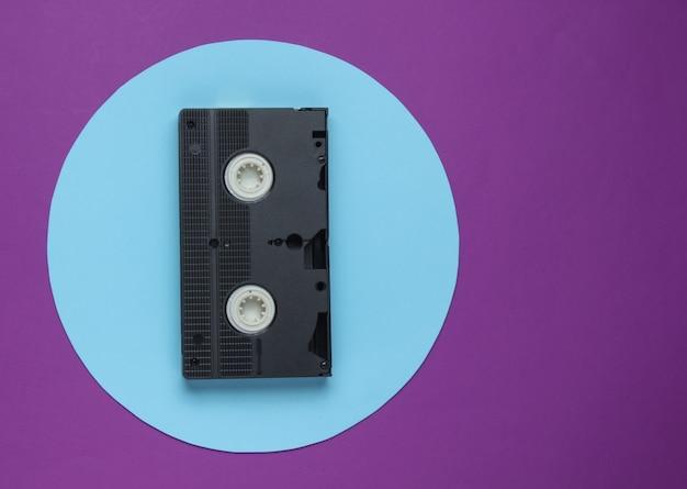 Cassette Vidéo Sur Fond Violet Avec Cercle Pastel Bleu. Concept Rétro Minimaliste. Vue De Dessus Photo Premium