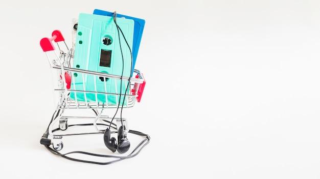 Cassettes dans un chariot avec des écouteurs sur fond blanc Photo gratuit