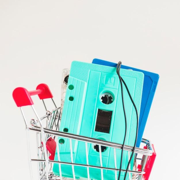 Cassettes turquoises et bleues dans un chariot sur fond blanc Photo gratuit