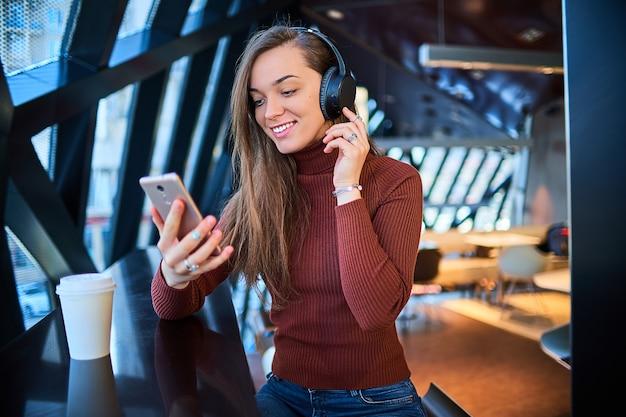 Casual Jeune Femme Heureuse Avec Un Casque Sans Fil Et Un Téléphone Mobile. Photo Premium
