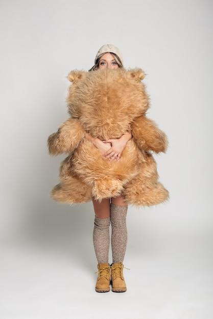 Casual Jeune Femme Souriante En Vêtements Tricotés Tenant Un Gros Ours En Peluche Doux Photo gratuit