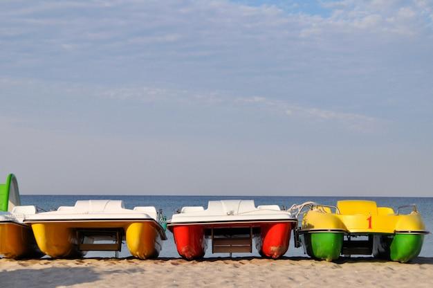 Catamarans colorés près du bord de mer sur une plage déserte à l'aube Photo Premium