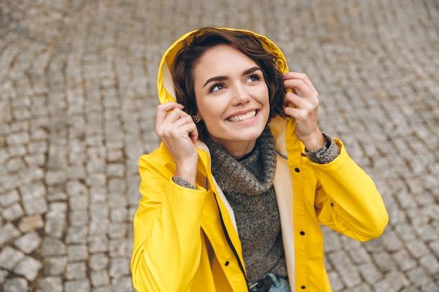 Caucasian Cute Female In Yellow Coat Wearing Hood Sur Regardant Vers Le Haut Se Réjouissant Du Temps Pluvieux En Marchant Dans Le Centre-ville Photo gratuit