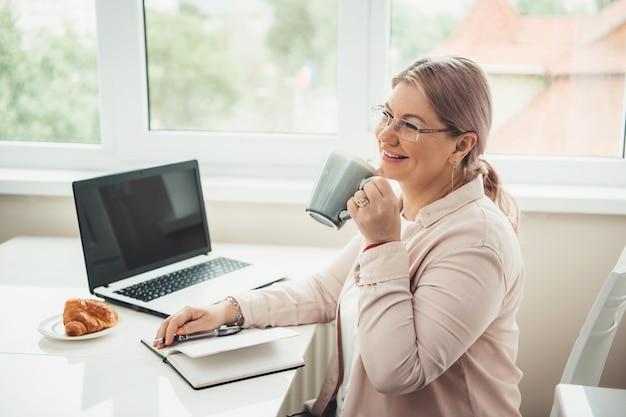 Caucasian Senior Woman Travaillant à L'ordinateur Portable De La Maison Tout En Buvant Du Thé Avec Croissant Et Sourire Photo Premium