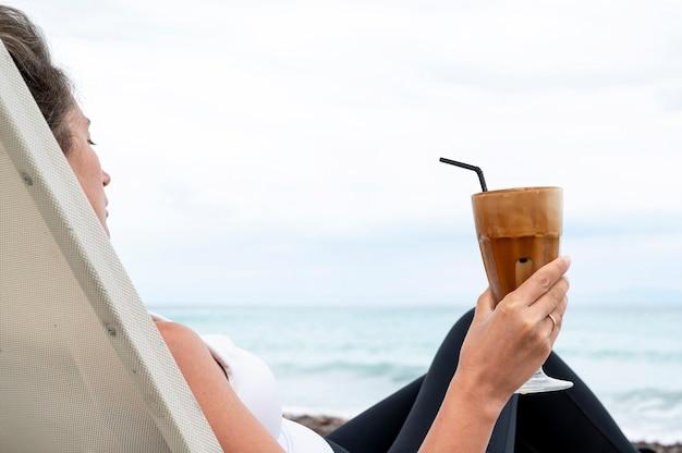 Caucasian Woman Holding Coffee Drink Sur Une Plage Avec De La Mousse Et De La Paille Avec Mer Photo gratuit