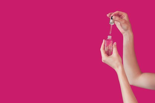 Caucasian Woman Holding Une Pipette Et Une Bouteille D'huile Essentielle Pour Les Soins De La Peau Sur Un Fond Violet Avec Un Espace Libre Photo Premium