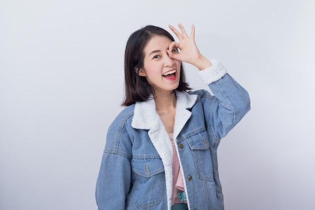Caucasien, femme souriante, projection, main, signe ok, positif, heureux, jeune fille asiatique, porter, bleu, vêtements décontractés, portrait Photo Premium