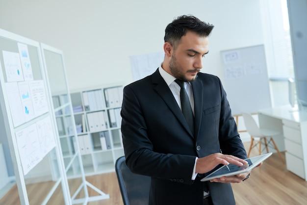 Caucasien, homme affaires, dans, intelligent, costume, debout, bureau, utilisation, tablette Photo gratuit