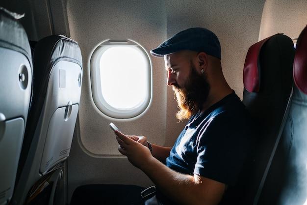 Caucasien, homme, utilisation, téléphone, avion Photo Premium