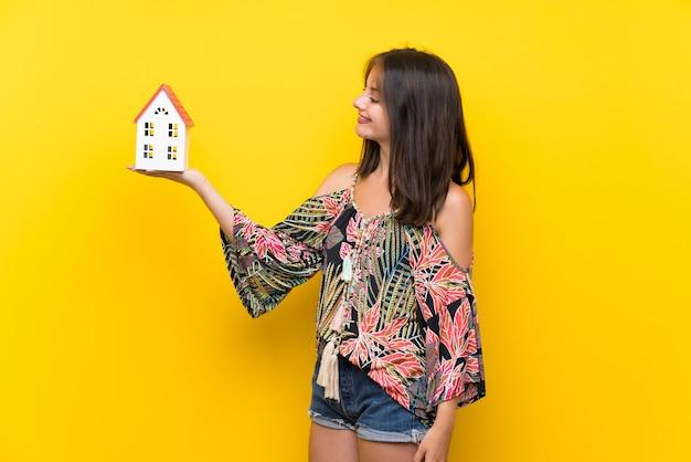 Caucasienne fille en robe colorée sur mur jaune isolé tenant une petite maison Photo Premium