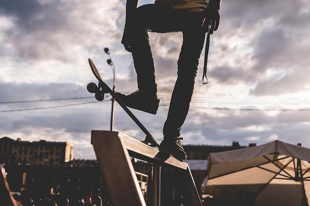 Cavalier debout sur une planche à roulettes avant le tour contre ciel Photo Premium