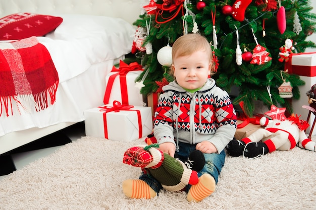 Célébration Du Nouvel An En Famille. Le Petit Boyl à L'arbre De Noël. Photo Premium