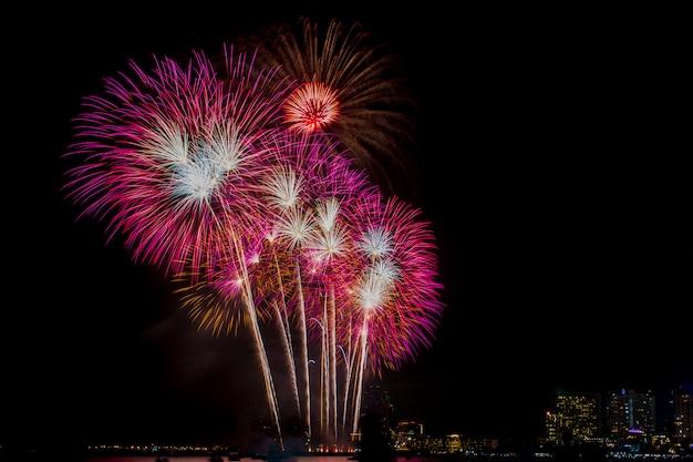 Célébration de feux d'artifice dans le ciel nocturne, fond du bâtiment. Photo Premium