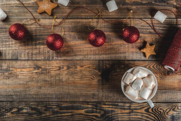 Célébrations de noël, du nouvel an. table en bois avec décorations, corde de fête, boules de noël, guimauve, tasse de chocolat chaud, fond de vue de dessus Photo Premium