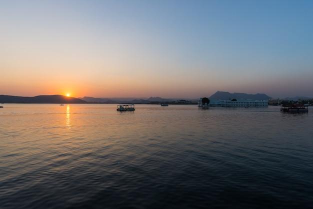 Le célèbre palais blanc sur le lac pichola au coucher du soleil. Photo Premium