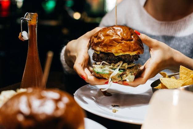 Célébrer avec un burger de boeuf juteux dans un restaurant Photo gratuit